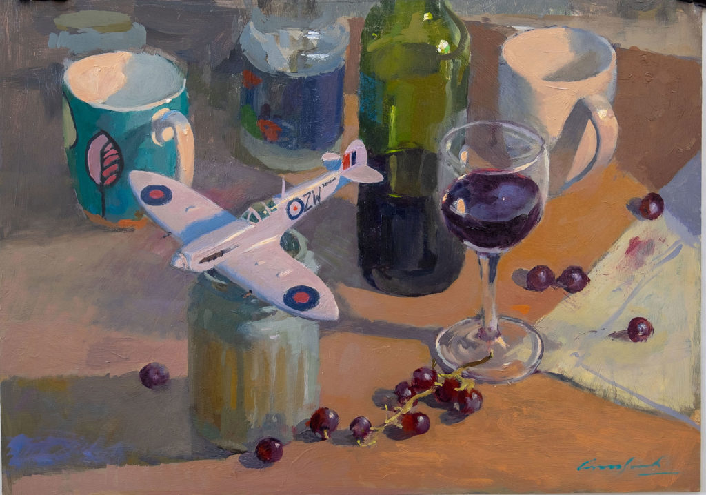 Oil painting of a toy aeroplane, a glass of red wine, a third full bottle of red wine, some red grapes and a few mugs used as props in the studio of Tasmanian artist Rick Crossland